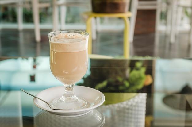 Heißer kaffee mit milch, auf einem tisch in einem café platziert.