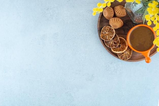 Heißer kaffee, orangenscheiben und süße kekse auf holzteller.