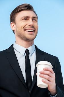 Heißer kaffee. porträt eines geschäftsmannes, der tasse kaffee hält und gegen den blauen himmel wegschaut