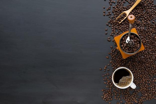 Heißer kaffee und bohne auf schwarzem holztischhintergrund. draufsicht