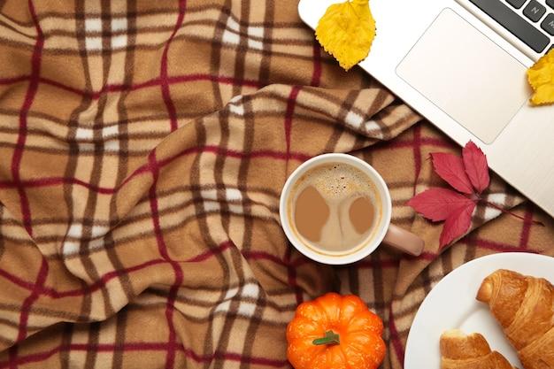 Heißer kaffee und herbstblätter mit notizbuch auf plaid - saisonales entspannungskonzept. ansicht von oben
