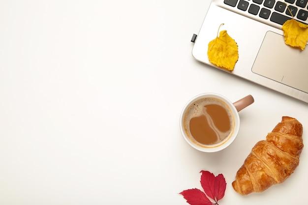 Heißer kaffee und herbstblätter mit notizbuch auf weiß - saisonales entspannungskonzept. ansicht von oben