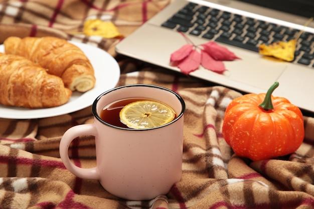 Heißer kaffee und herbstlaub mit notizbuch auf plaid - saisonales entspannungskonzept