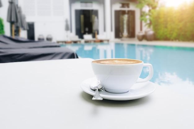 Heißer kaffee und lattekunst am poolbett mit morgenlicht