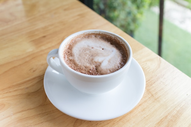 Heißer kaffeemokka mit schaummilch im landschaftscafé
