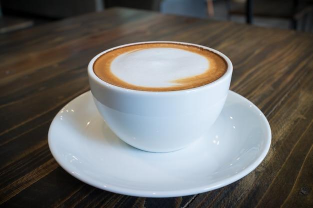 Heißer kaffeemokka mit schaummilchkunst im weinlesecafé