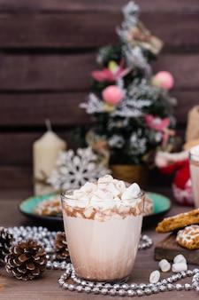 Heißer kakao mit eibischen in den gläsern auf einem holztisch mit weihnachtsdekorationen