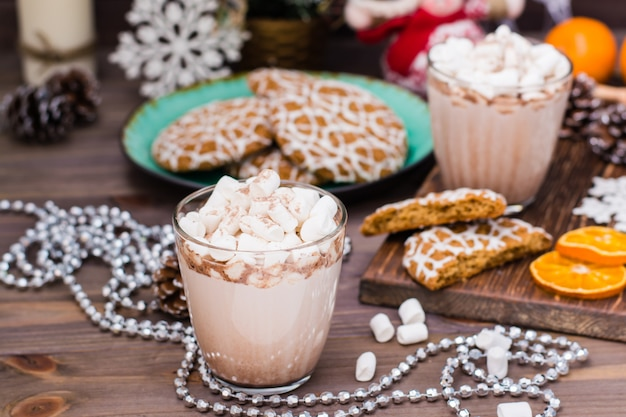 Heißer kakao mit eibischen in den gläsern und in den weihnachtsplätzchen auf einer platte auf dem holztisch mit weihnachtsdekorationen