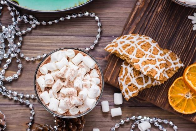Heißer kakao mit eibischen und zimt in den gläsern auf dem tisch mit weihnachtsdekorationen. ansicht von oben