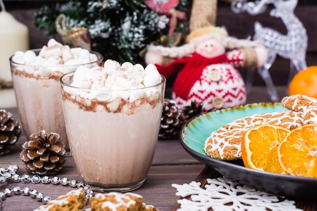 Heißer kakao mit eibischen und zimt in den gläsern auf tabelle mit weihnachtsdekorationen
