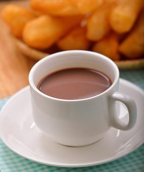 Heißer kakao mit frittiertem teigstab zum frühstück