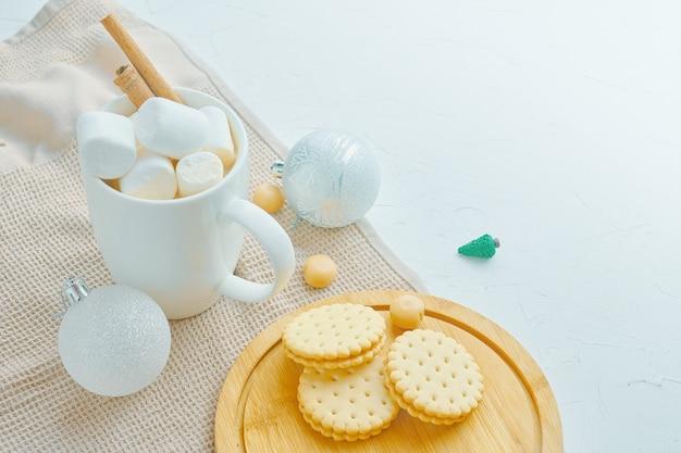 Heißer kakao mit keksen, marshhamllows, zimt, weihnachtsschmuck, miniatur-weihnachtsbaum
