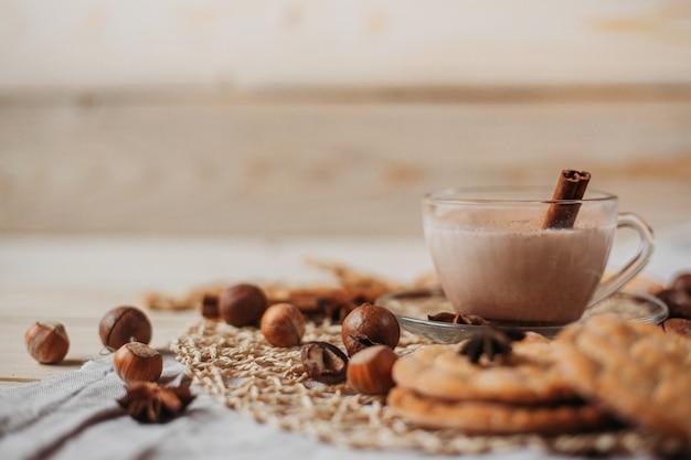 Heißer kakao mit keksen, zimtstangen, anis, nüssen auf holztisch. vorderansicht, kopierraum.