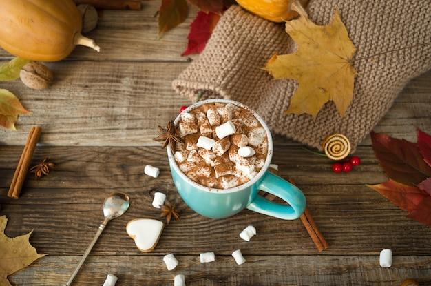 Heißer kakao mit marshmallows in einem blauen keramikbecher mit herbstlaub und kürbissen auf einem holztisch. das konzept von hygge, gemütlichem herbst, thanksgiving, herbst. heiße getränke. herbststillleben.