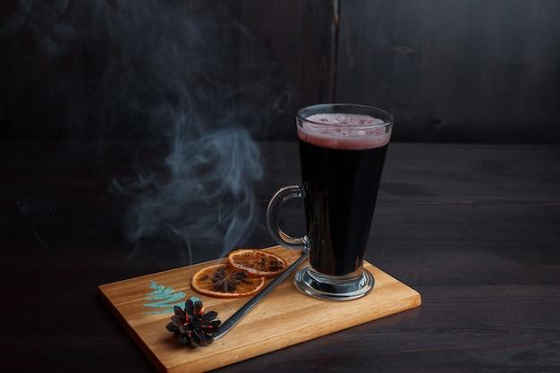 Heißer köstlicher würziger glühwein, garniert mit getrockneten orangenscheiben und einer schwelenden beule auf einem holzbrett in einem restaurant. tolles wintergetränk.