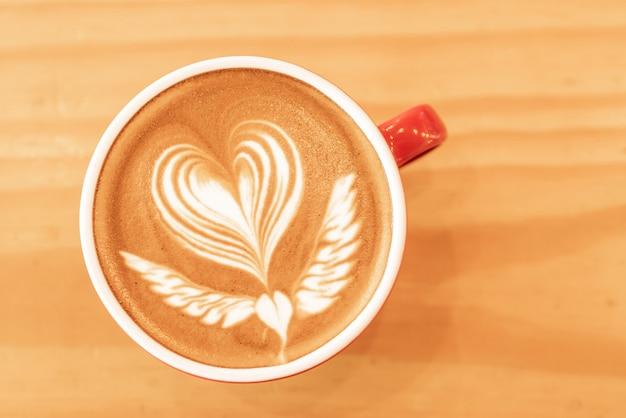 Heißer kunstkaffee-cappuccino in einer schale auf holztischhintergrund mit kopienraum