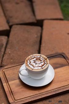 Heißer latte-art-kaffee auf holztisch, zeit zum entspannen