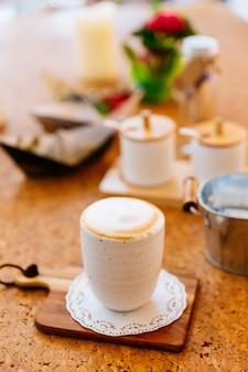 Heißer latte diente in der keramischen schale auf hölzerner platte. glatter weißer und brauner schaum.