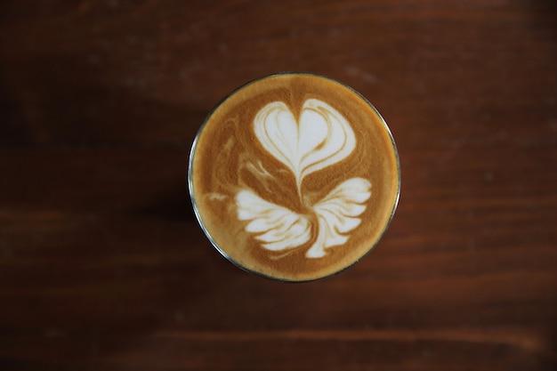 Heißer latte-kaffee auf holzhintergrund