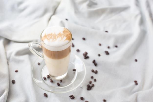 Heißer latte-kaffee in einem klaren glas verjüngt.