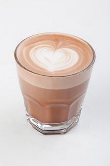 Heißer latte mit dekoration in einem transparenten becher auf weißem hintergrund