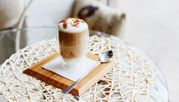 Heißer latte- oder cappuccino-kaffee auf dem tisch im café oder in der küche in der nähe des fensters mit kopienraummorgenkaffee-latte mit milch und schokolade oben in doppelwandigem glas auf servierbrett mit löffel