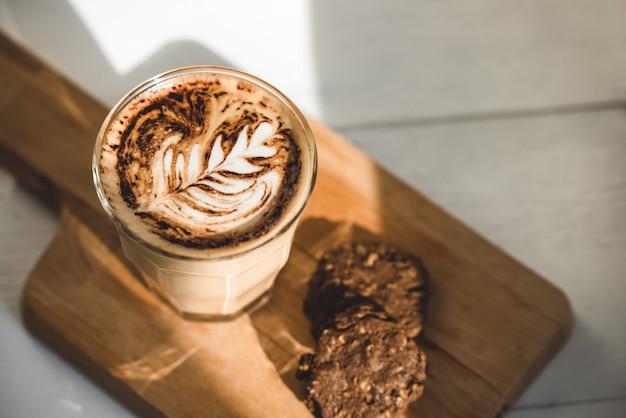 Heißer lattekaffee im becherglas mit schokoladenplätzchen