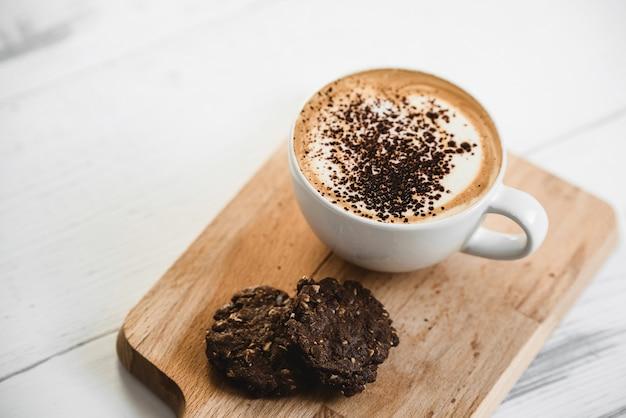 Heißer lattekaffee in der tasse mit schokoladenkeksen