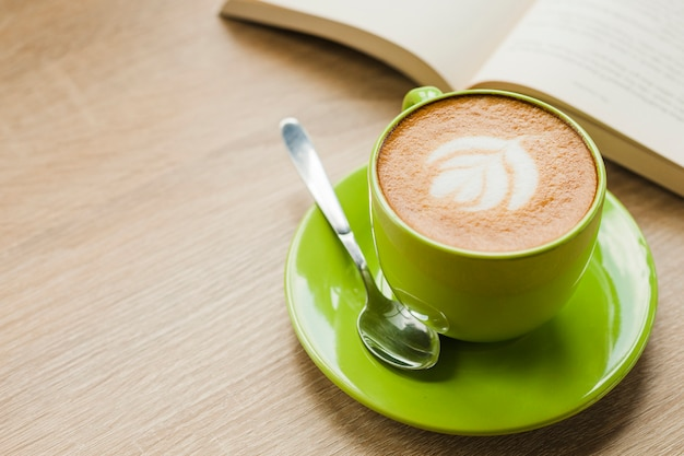 Heißer lattekaffee mit lattekunst in der grünen schale auf tabelle