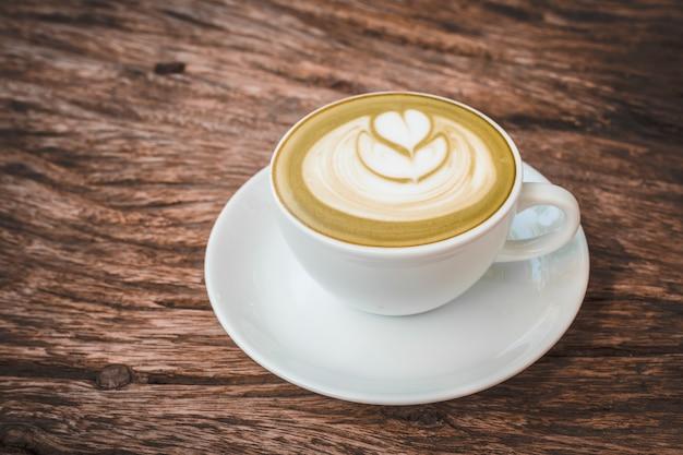 Heißer lattekunstkaffee auf hölzernem hintergrund