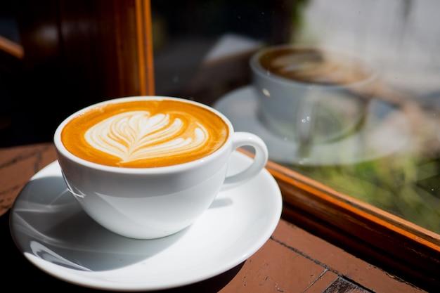 Heißer lattekunstkaffee auf hölzerner tabelle, entspannen sich zeit