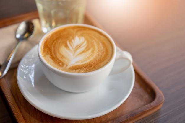 Heißer lattekunstkaffee in der weißen schale mit metalllöffel auf holztischhintergrund