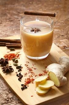Heißer masala tee. belebender tee mit gewürzen, indischem rezept, den zutaten auf dem brett. vertikal