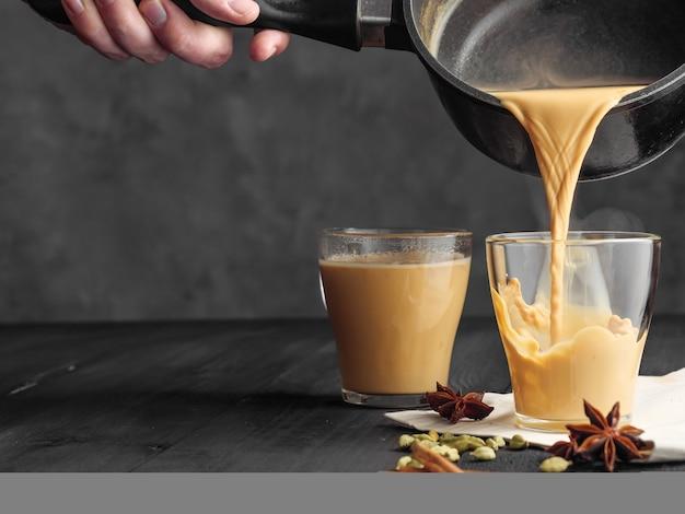 Heißer masala-tee wird in ein glasglas gegossen. aus dem becher kommt dampf.