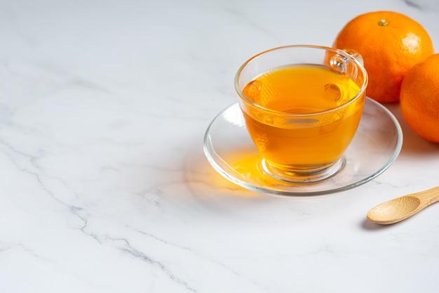 Heißer orangentee und frische orange auf dem tisch