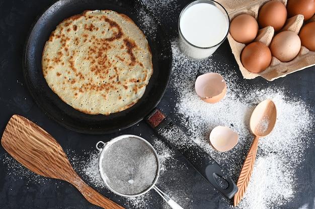 Heißer pfannkuchen in schwarzer pfanne auf schwarzem tisch mit mehl, milch und eiern.