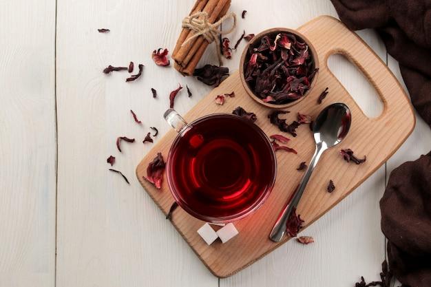 Heißer roter karkade-tee in glasbechern mit trockenem tee auf einem weißen holztisch. draufsicht.