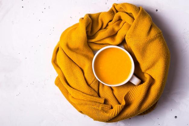 Heißer sanddorn-früchtetee mit einem warmen strickpullover. herbstsaison