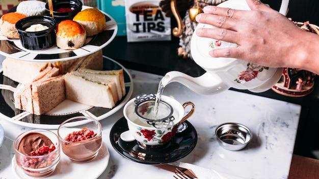 Heißer schmetterlingserbsen-blaubeer-tee, der aus dem becher durch einen tee-tee aus edelstahl gegossen wird.