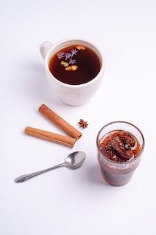 Heißer schwarzer aromatischer tee nahe feigenmarmelade, weihnachtsfrühstücksstimmung mit anis und zimt auf weißer oberfläche, winkelansicht