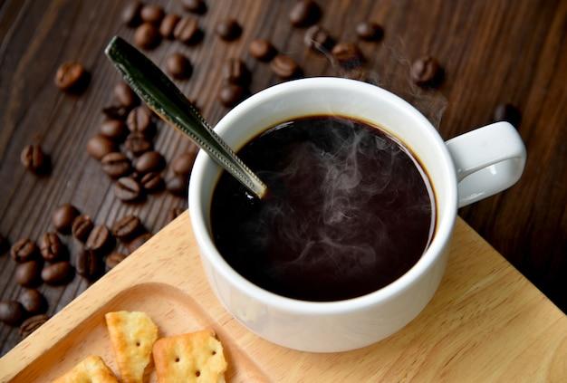 Heißer schwarzer kaffee auf becher mit crackers kern ananas-rühren