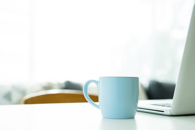 Heißer schwarzer kaffee in der blauen kaffeetasse auf dem tisch hautnah mit exemplar. heißer americano-kaffee in der blauen keramik-kaffeetasse hautnah.