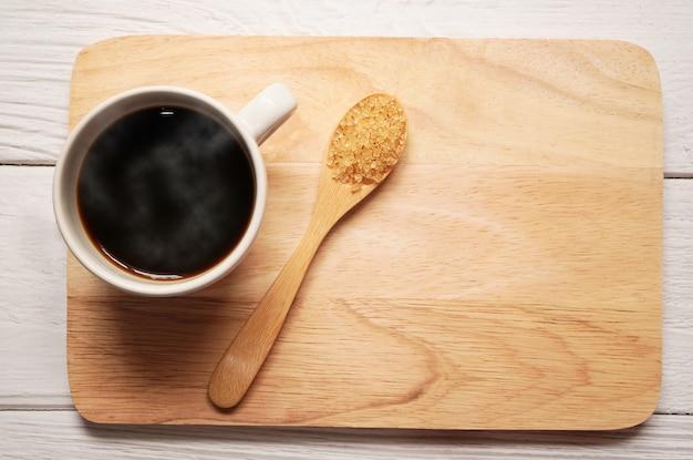 Heißer schwarzer kaffee mit braunem zucker im holzlöffel auf holzteller