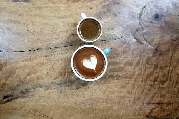Heißer schwarzer kaffee mit später kunst auf tisch