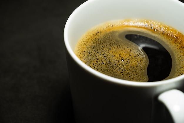 Heißer schwarzer kaffee und blasen der nahaufnahme in der weißen schale gegen dunklen hintergrund