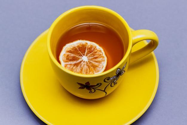 Heißer schwarzer tee mit draufsicht der zitronenscheibe auf grauem hintergrund. gelbe tasse auf grau. farben des jahres 2021.