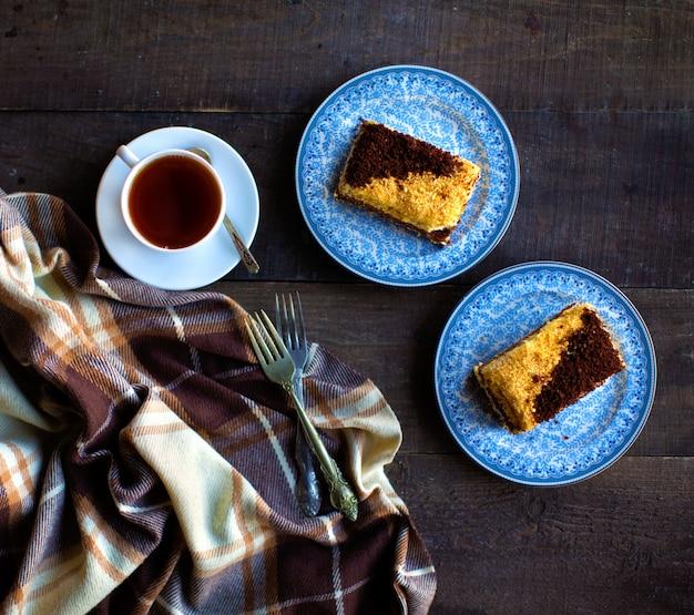 Heißer schwarzer tee mit kuchenstücken