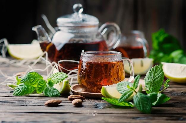 Heißer schwarzer tee mit zitrone und minze auf dem holztisch