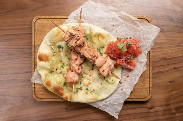 Heißer schweinefleischspiesse mit tomaten, zwiebeln und frisch gebackener tortilla auf einem hölzernen schneidebrett.