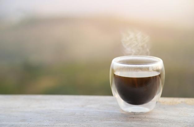 Heißer strömender kaffee mit verschwommener naturansicht
